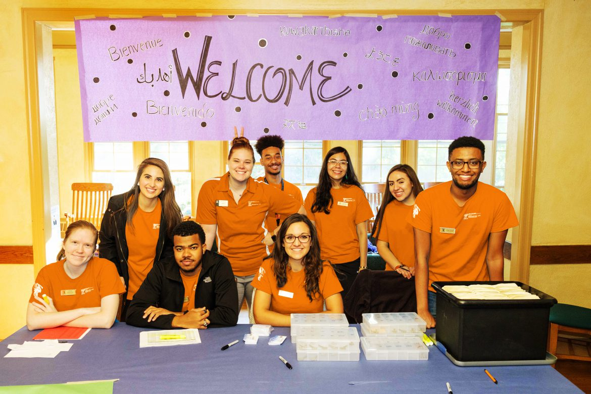 Welcome sign and upperclass students at welcome table