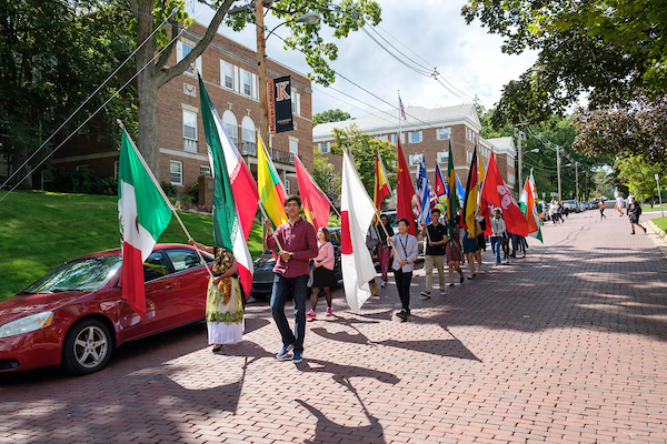Incoming students from different countries walk down Academy Street carrying the flags of their home countries.